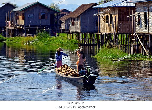 two women transporting wood in a boat on a waterway through a village south of Inle Lake, Burma, Shan-Staat