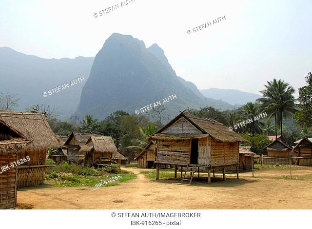 Village of the Khmu ethnic group with huts made of bamboo in front of cone-shaped mountains near Luang Prabang, Laos, Southeast Asia