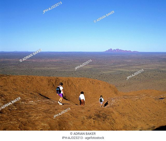 Uluru-Kata Tjuta National Park - Tourists at the top of Ayers Rock Uluru with view of the Olgas in the Distance