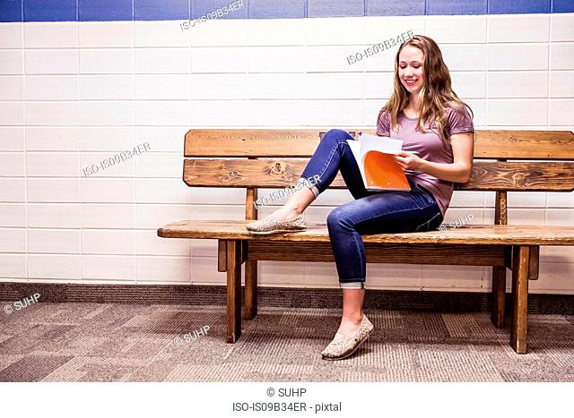 Teenage high school girl sitting on bench reading notebook in corridor