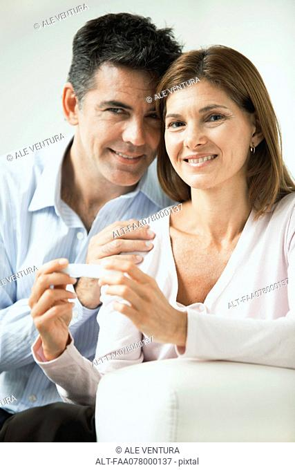 Couple smiling, woman holding pregnancy test