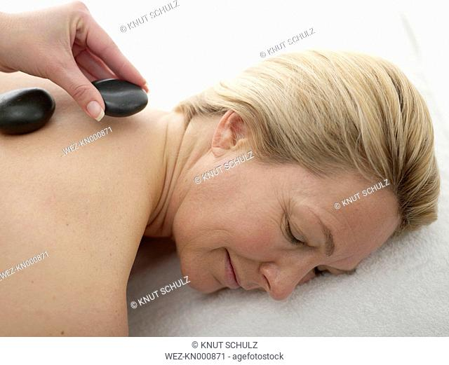 Mature woman receiving hot stone therapy, close up