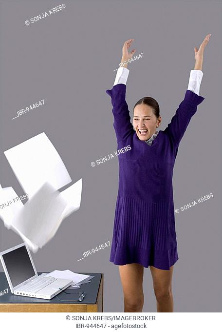 Young woman throwing sheets of paper around