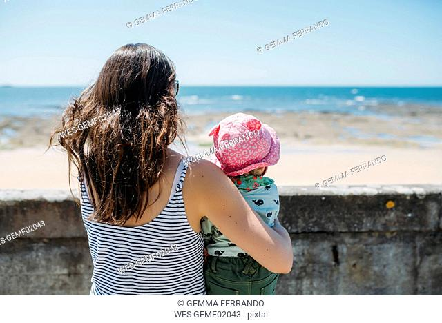 France, back view of mother and baby girl looking to the sea