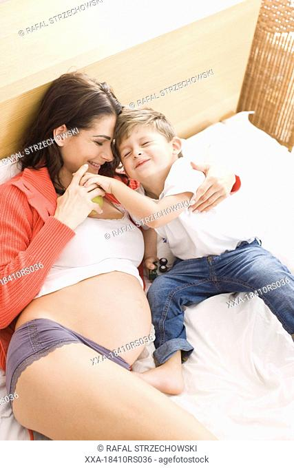 Pregnant woman playing with son in bed