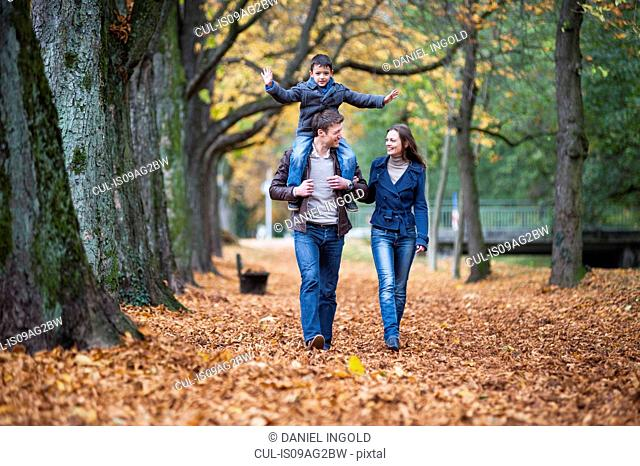Family strolling through autumn leaves in park