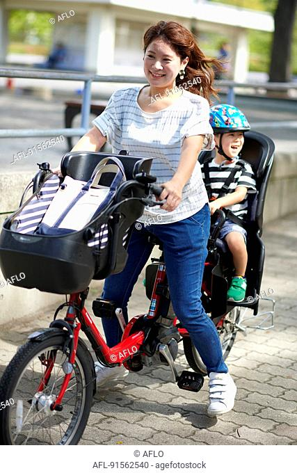 Japanese mother and kid riding a bike