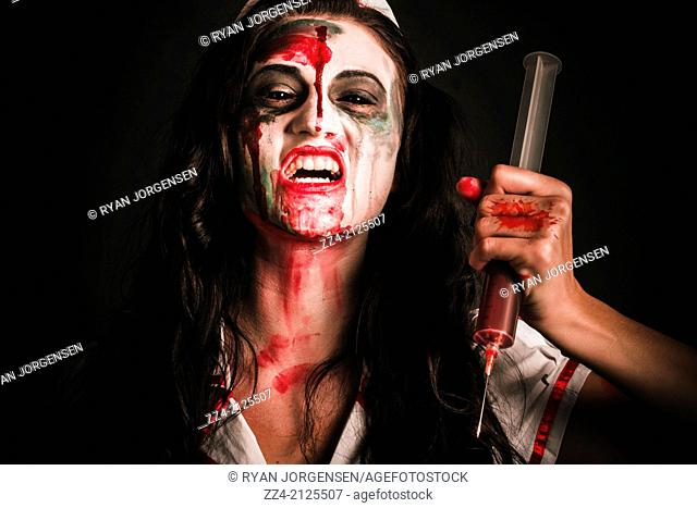 Horror movie scene on the face of a creepy nurse about to stab patient with big needle. Injection of sickness