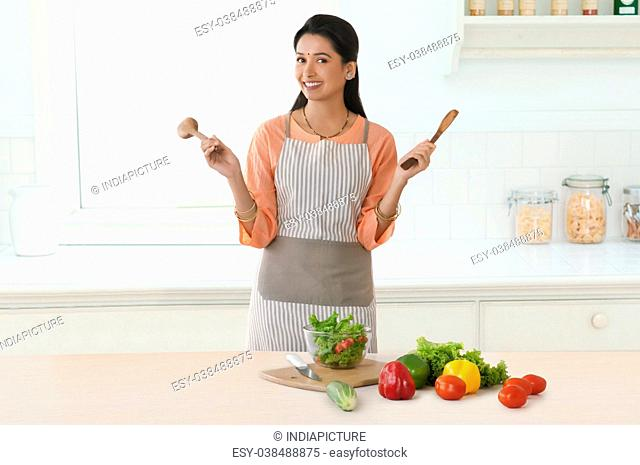 Woman holding wooden spatulas in kitchen