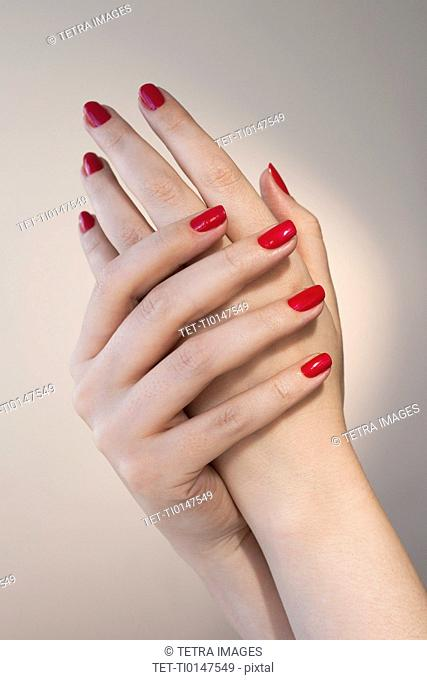 Close up of woman's hands with red nail polish