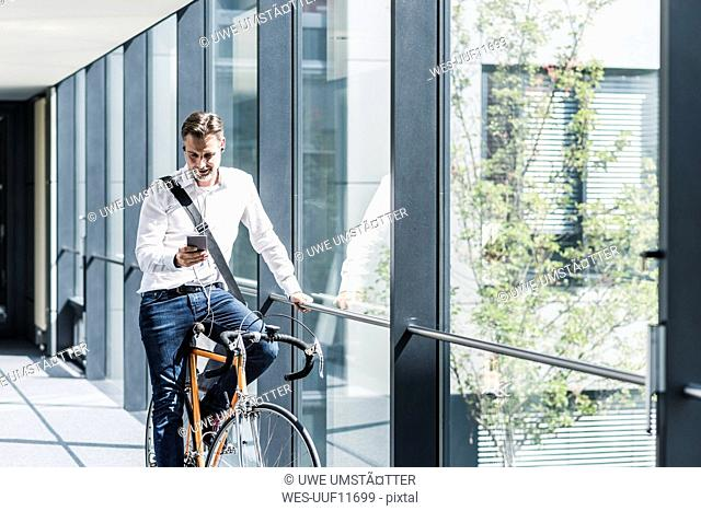 Businessman with cell phone on bicycle in office passageway