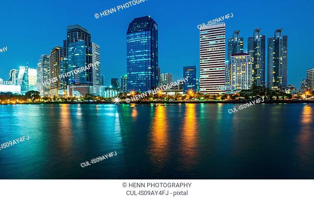 View across river of skyscrapers on skyline, Benjakiti Park, Bangkok, Thailand
