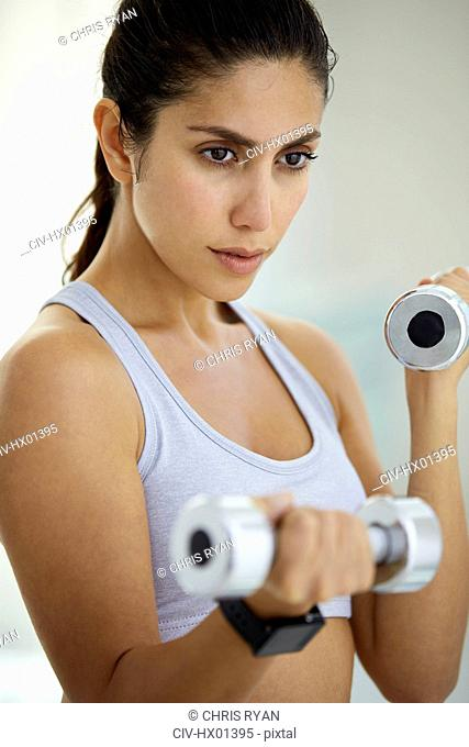 Determined brunette woman doing biceps curls with dumbbells
