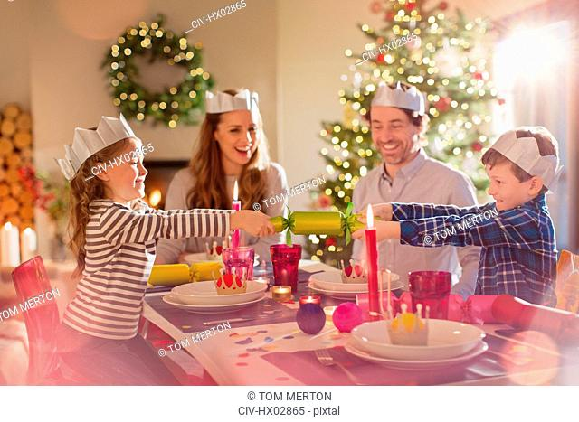 Family in paper crowns pulling Christmas cracker at dining table