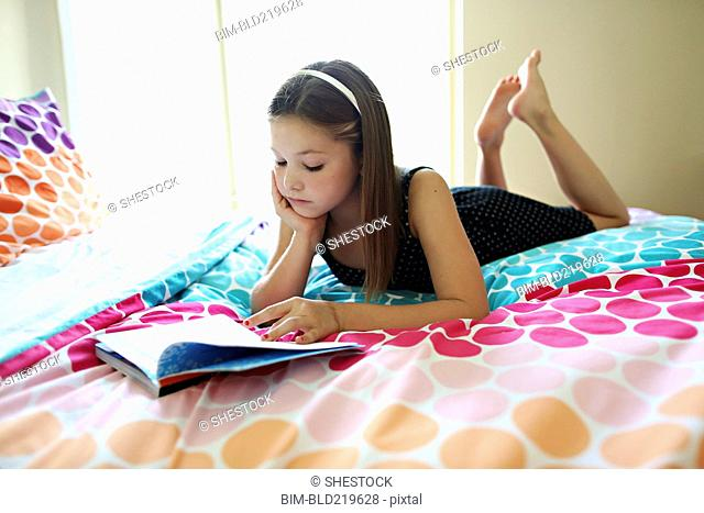 Calm girl reading book on bed