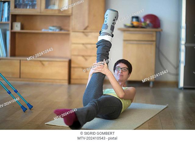 Woman doing stretch exercise with a broken leg