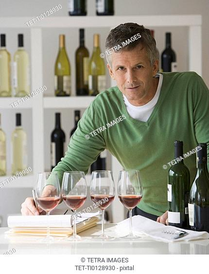 Man behind row of wine glasses