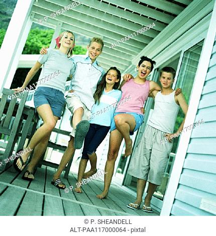 Young people standing with arms around each other's shoulders on porch
