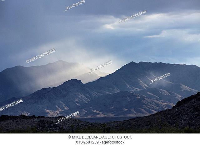 A late afternoon thunder storm builds in the mountains surrounding the Mojave Desert that split the sunlight into shafts of light slicing through the valley
