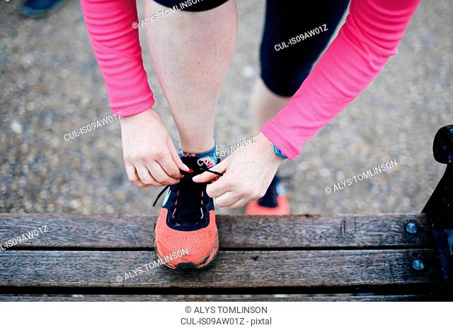 Overhead cropped view of woman tying trainer laces on park bench