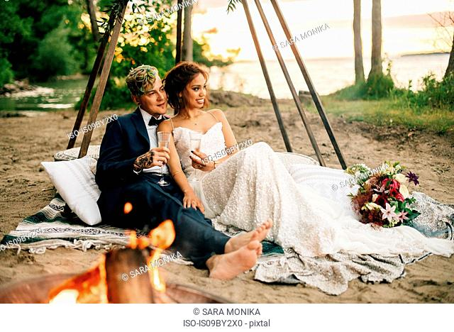 Bride and groom on picnic blanket by lakeside campfire, Lake Ontario, Toronto, Canada