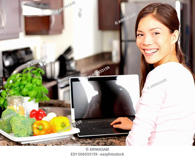Woman using laptop computer in kitchen with greens and vegetables. Lifestyle cooking concept with smiling happy mixed-race Asian chinese Caucasian woman working...