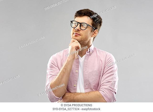 thinking young man in glasses over grey background