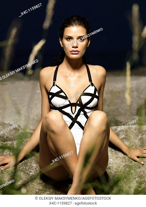 Beautiful young woman in white swim suit siting on a rocky shore  High fashion photo