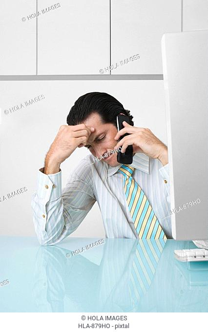 Businessman talking on a mobile phone and sitting in an office
