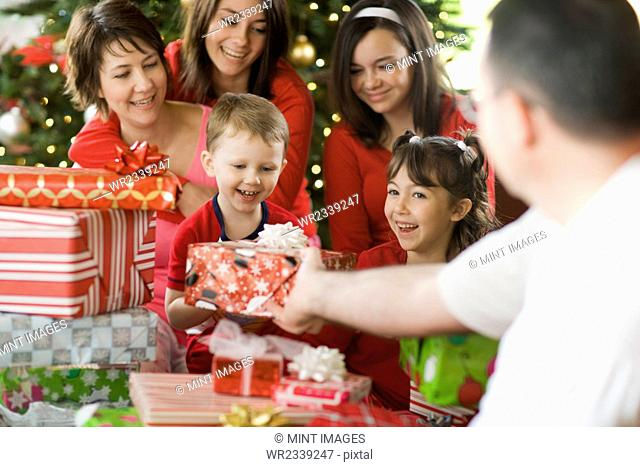 A group of people, parents and children, family exchanging presents on Christmas morning
