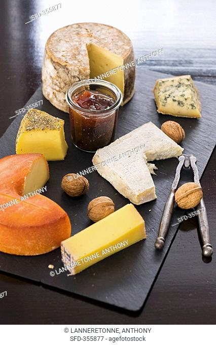 A cheese platter with nuts and jam