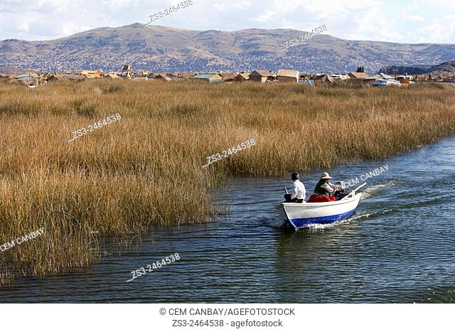 Aymara people in a rowing boat, Uros Islands, Lake Titicaca, Puno, Peru, South America