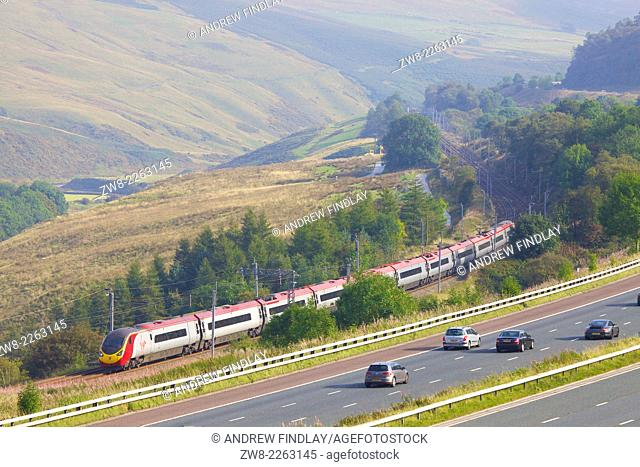 Class 390 Pendolino Virgin train passing the M6 motorway in the River Lune Valley. Howgills, Cumbria, West Coast Main Line, England, UK