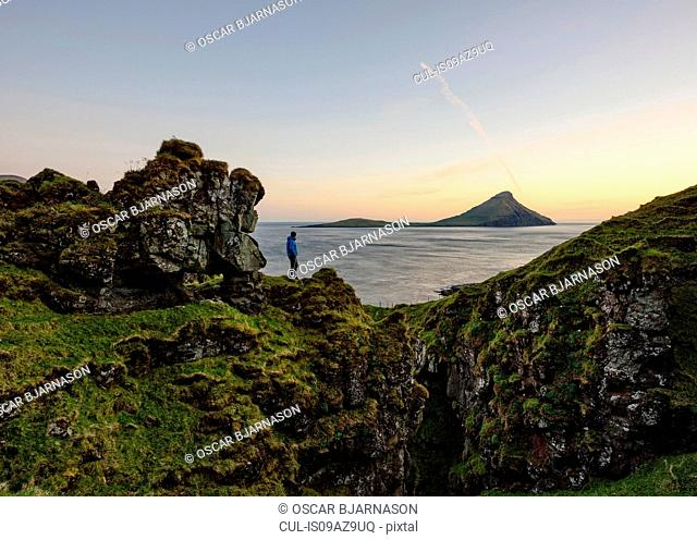 Man on cliff looking at Koltur island in ocean, Velbastadur, Faroe Islands