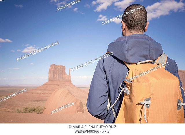 USA, Utah, back view of man with backpack looking at Monument Valley