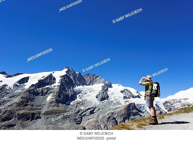 Austria, Carinthia, man, hiker with binoculars watching Grossglockner peak, High Tauern National Park