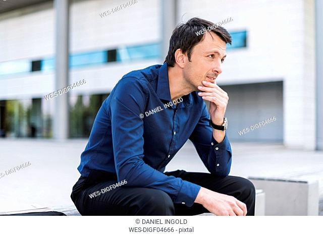Businessman sitting outdoors thinking