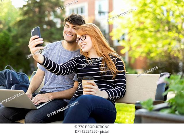 A young man and young woman sit together on a bench on the university campus taking a self-portrait on a smart phone while drinking coffee; Edmonton, Alberta