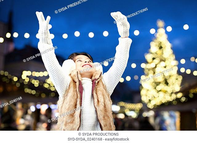 happy girl wearing earmuffs over christmas lights