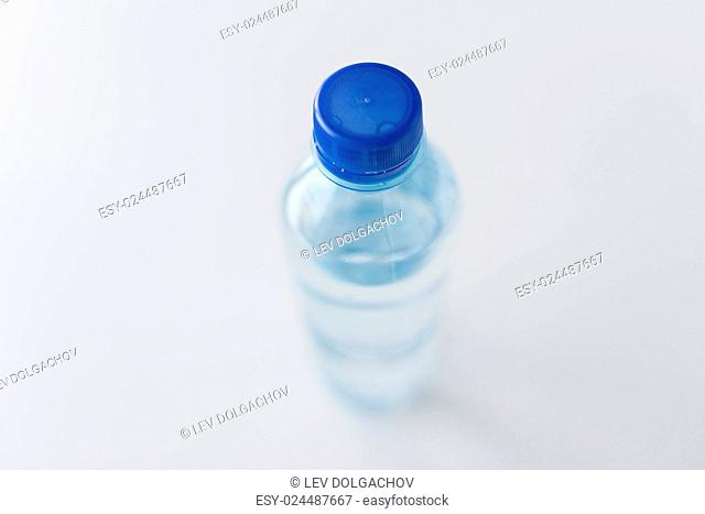 recycling, healthy eating and food storage concept - close up of plastic bottle with pure drinking water on table