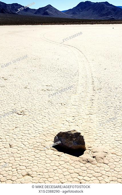 Rock boulder cuts a trail in the dry lake bed in Death Valley
