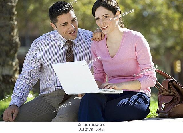 Businessman and businesswoman sitting on wall, woman using laptop in lap, smiling