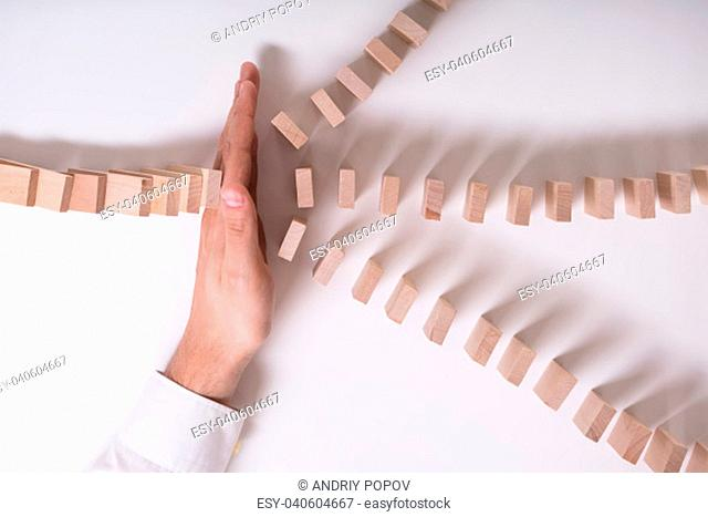 Close-up Of A Businessperson's Hand Stopping Wooden Blocks From Falling On White Background