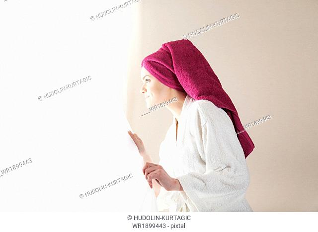Young woman in bathrobe looking out of window