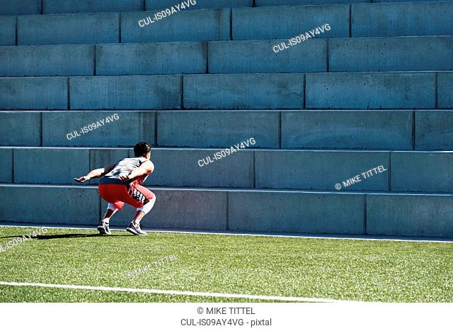 Young man training, preparing to jump up playing field stairway