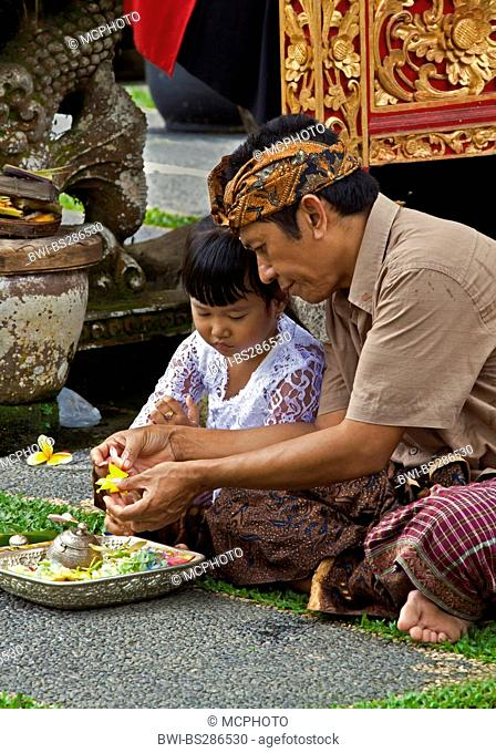 Father and daughter make puja at PURA TAMAN SARASWATI during the GALUNGAN FESTIVAL , Indonesia, Bali, Ubud