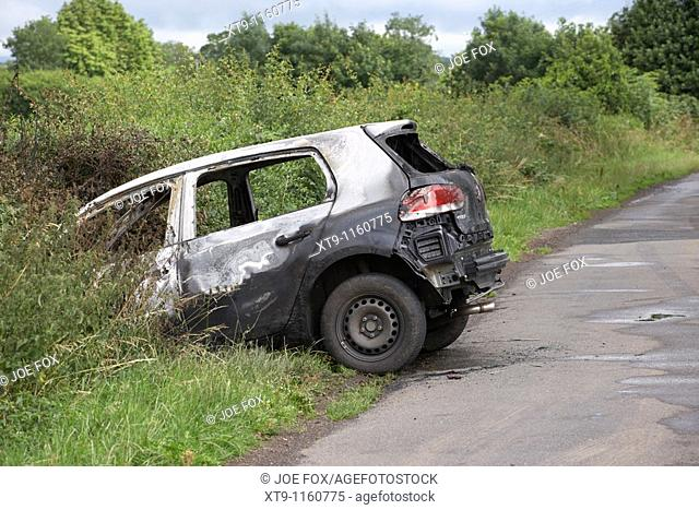burned out stolen volkswagen golf car crashed into a ditch in northern ireland in the uk