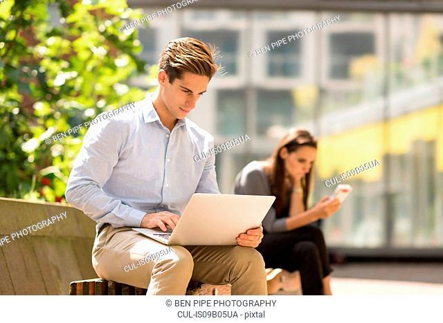 Businessman typing on laptop in city, London, UK