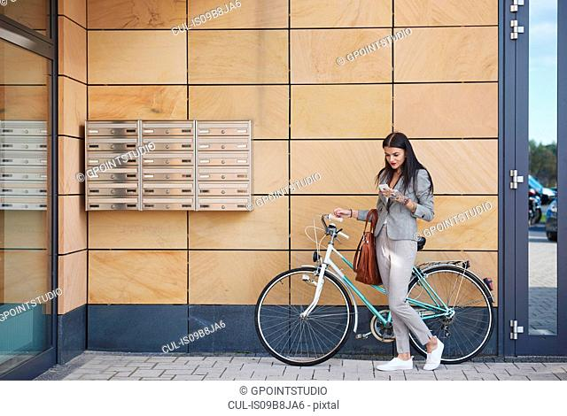 Businesswoman beside office building, walking bicycle, using smartphone