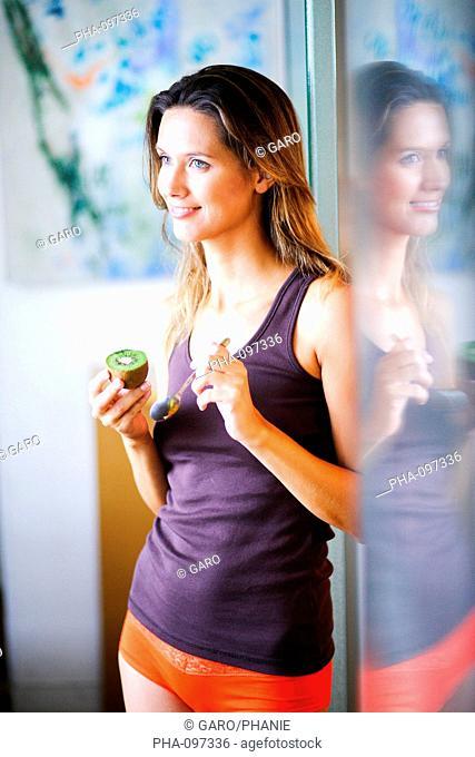 Woman eating kiwi fruit